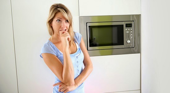 woman-anxious-in-front-of-microwave
